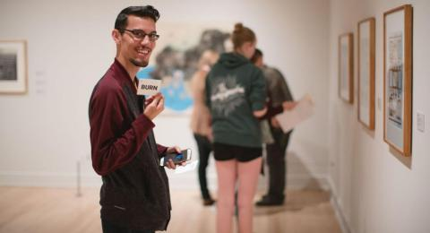 Young man in art gallery smiling at camera holding up a card with other people in background looking at art