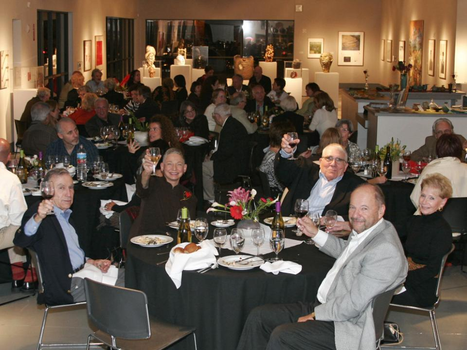 Fancy gala with middle-aged patrons sitting at round black tables in art gallery with people at foreground table holding up wine glasses and smiling at camera for cheers