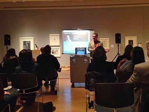 Jan Fisher giving lecture to small audience in art gallery