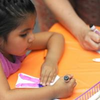 Little girl coloring with markers with adult in background