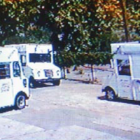 Video still image from surveillance footage of three ice-cream trucks facing each other from three different angles