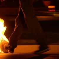 Video still image of persons legs walking and kicking round object that is on fire