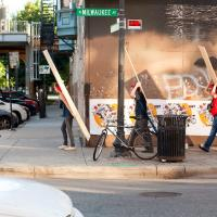 Photo of five people walking down the street carrying large flat boards in an urban setting