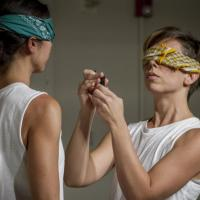 Two women blindfolded facing each other wearing sleeveless white tshirts
