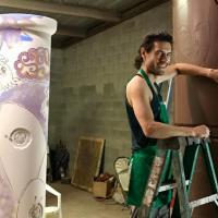 Artist Tom Franco smiling at camera while working on very large ceramic sculpture